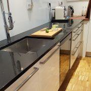 Küchenblock mit schwarzer Natursteinarbeitsplatte und Edelstahlunterspüle