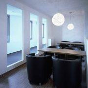 Tische mit Edelstahlbein an Trennwand befestigt
