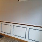Seitenverkleidung eines alten Treppenhauses mit Rahmen und Füllungen in Farbton weiß/grau