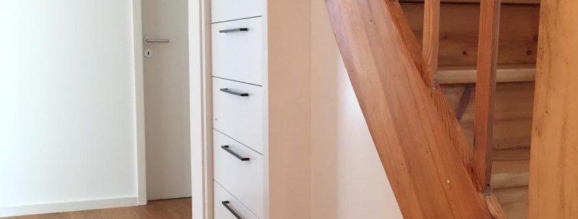 Einbauschrank in weiß lackiertem Material unter Treppenlauf